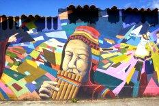 Diese Person spielt die Panlöte, die besonders aus den Anden bekannt ist.